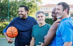 A group of middle aged men on an outside basketball court.