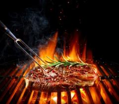 A steak being grilled on a bar-b-que.
