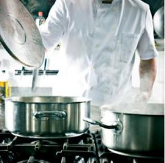 An image of a chef opening a stainless steel pot on a cooktop.