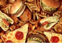 An image of fatty foods, including hamburger, fries, and pizza.