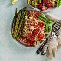 A bowl of sorghum with tomatoes and asparagus.