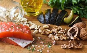 Healthy foods displayed on a table, including salmon, garlic, avocado, and walnuts.