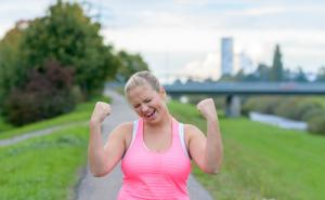 An picture of a woman wearing a pink top, giving a celebratory fist pump above her head.