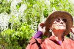 Image of an eldering woman wearing a hat and looking up toward the sun.