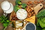 A display of food items including milk, nuts, cheese, sardines, and broccoli.