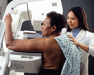An Asian female technician positions an African-American woman at an imaging machine to receive a mammogram.
