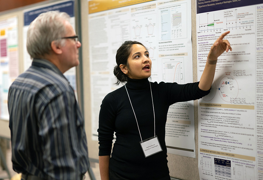 DCP's Dr. Matthew Young reviews a poster presentation by Aasthaa Bansal.