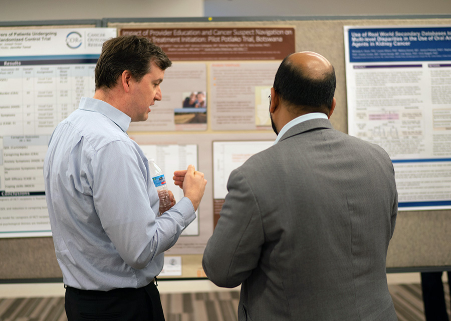 New Grantee Scott Dryden-Peterson talks with DCP's Dr. Vikrant Sahasrabuddhe.