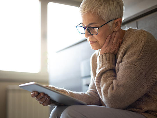 An older woman reading a tablet.