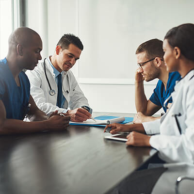 A meeting of 4 medical professional around a table.