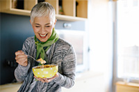 Image of a woman eating healthy foods.