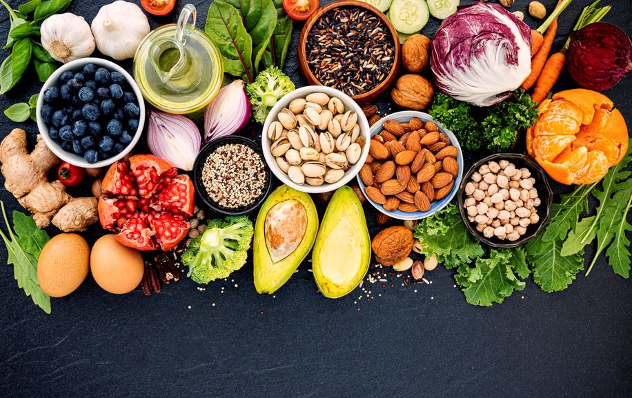 An image of healthy foods, including vegetables, nuts, and eggs.