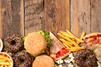 An image of donuts, hamburgers, french fries and pizza on a table.