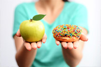 A picture of a person holding an apple in one hand and a donut in the other hand.