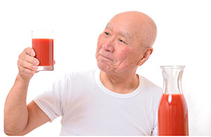 Image of a man holding up a glass of tomato juice.