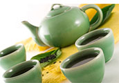 Image of a tea pot with four cups of tea