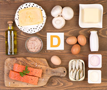 An image with olive oil, fish, eggs, and dairy products on a table.