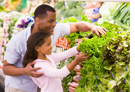 Image of a father and daughter selecting lettuce at a farmers market.