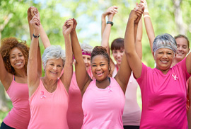 A group of women wearing pink t-shirts holding hands with their arms raised.
